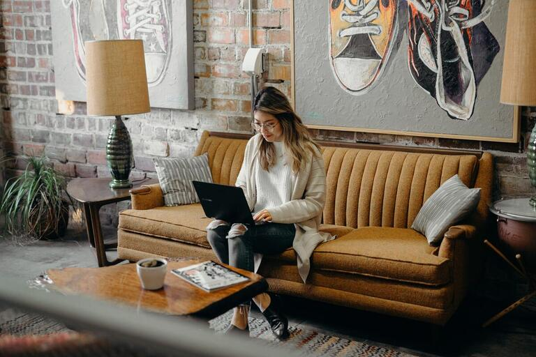 woman on couch working on a laptop