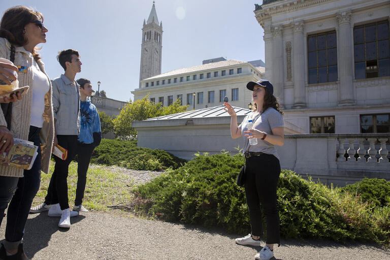 A tour guide speaks to a group of visitors in front of Doe Library