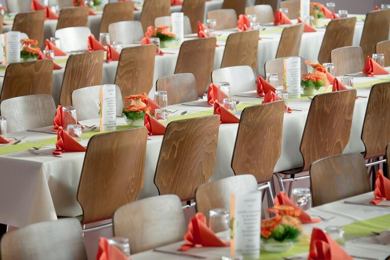 Rows of tables set with color place settings