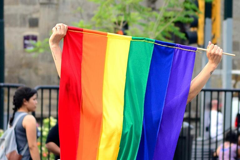 A rainbow pride flag is held up, the person holding it is hidden behind the large flag