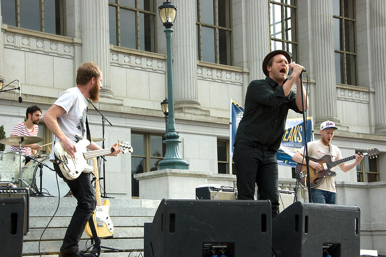 A man wearing all black sings into a microphone that he is holding with both hands, standing on the steps of Doe library. Guitarists and a drummer can be seen in the background
