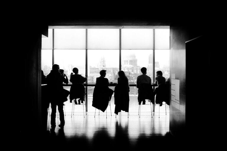 silhouettes of people in a room speaking to one another in pairs