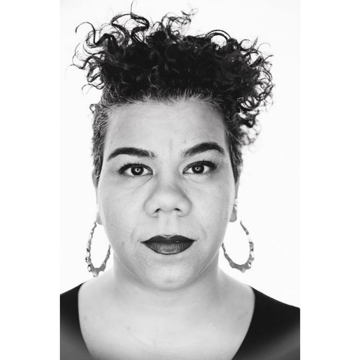 Black and white image of a woman with short dark curly hair stares into the camera. She wears large hoop earrings