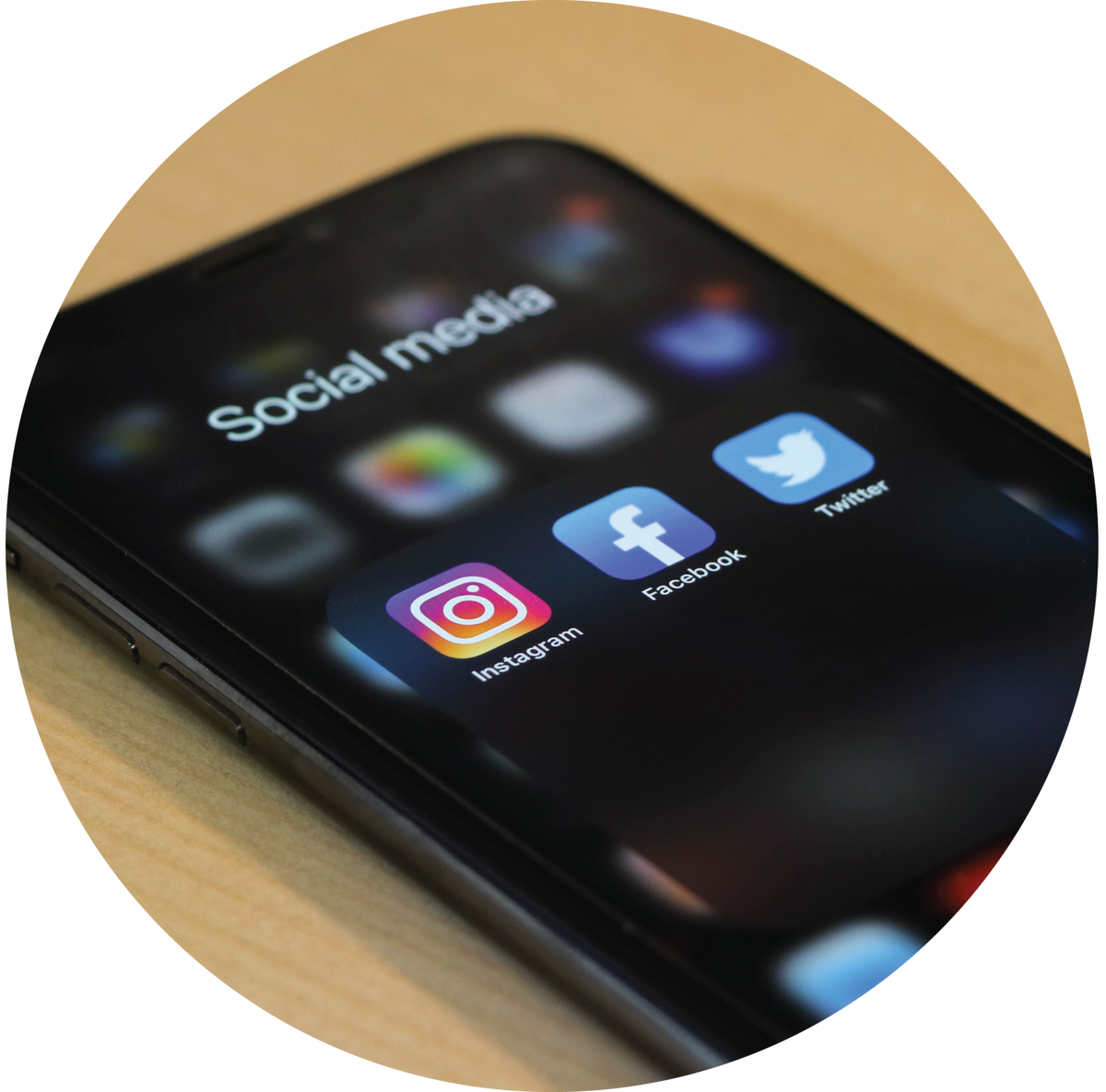 An iPhone showing icons for Instagram, Facebook, and Twitter apps