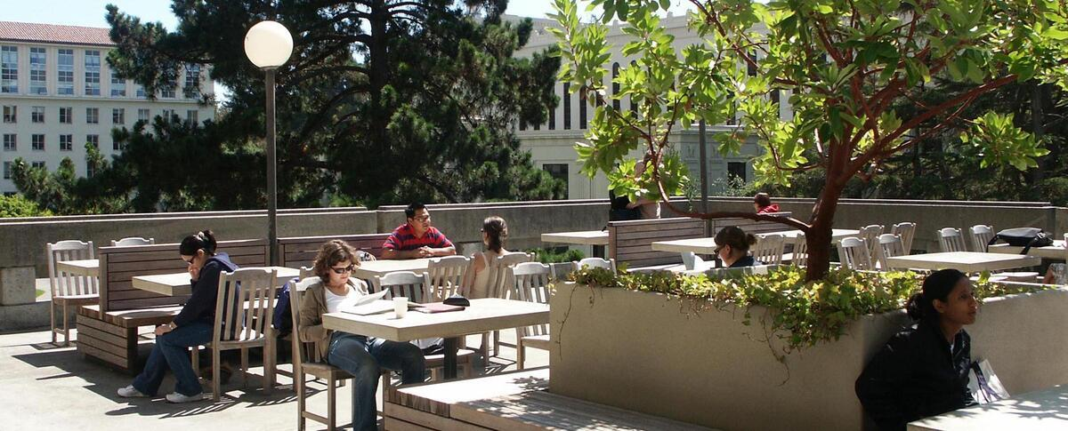 People sitting at tables on the patio of the Free Speech Movement Cafe at Moffit Library
