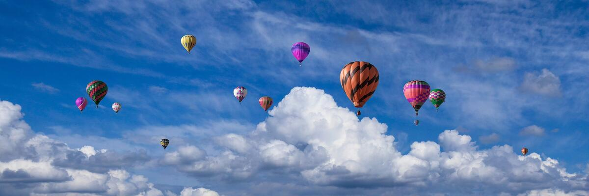 Colorful hot air balloons in cloudy sky
