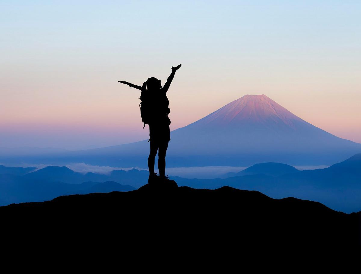 Silhouette of a person with their arms in the air standing on top of a mountain