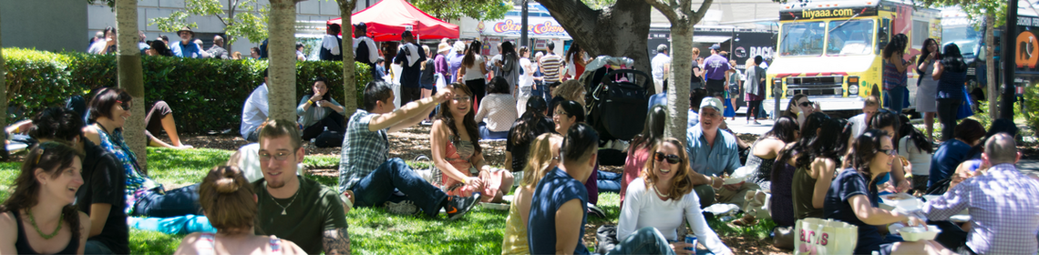 Many staff sitting on a grassy area with a food truck visible in the background