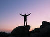 Silhouette of a person with their arms in the air standing on top of a rock with a sunset in the background
