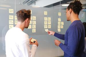 Two people working together to arrange post its on a wall
